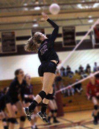 Teen girl spiking a volleyball over a net